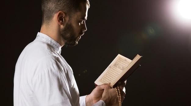 Evento de ramadam e homem árabe lendo tiro médio Foto gratuita