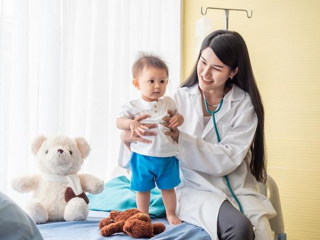 Exame médico bonito um menino na cama do paciente. Foto Premium