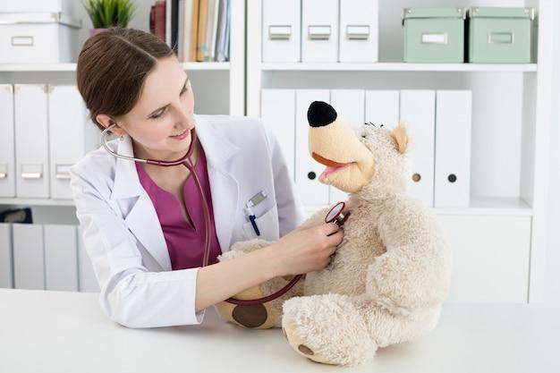 Exame médico de família. linda médica sorridente no jaleco branco examinar o ursinho de pelúcia com estetoscópio para acalmar e interessar a criança. brincando com o paciente bebê. conceito médico pediátrico Foto Premium