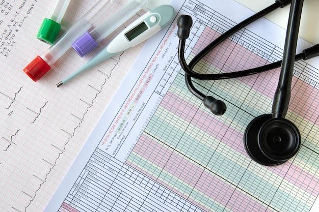 Exames de sangue, um termômetro digital e um estetoscópio em cima de uma mesa Foto Premium