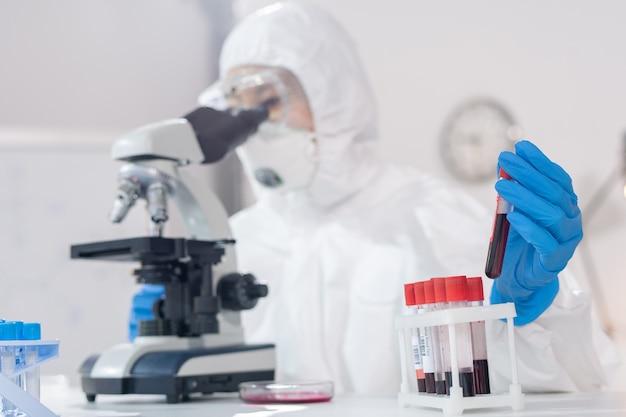 Examinando amostras de sangue no microscópio Foto Premium