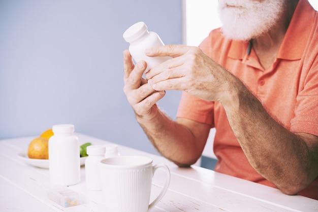 Examinando o frasco de comprimidos Foto gratuita