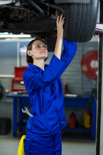 Examinar carro travão de disco da roda do mecânico feminino Foto gratuita
