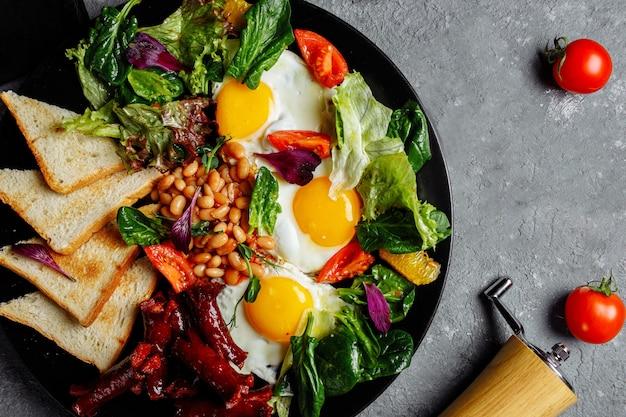 Excelente café da manhã com ovos fritos, torradas, alface e tomate. Foto Premium