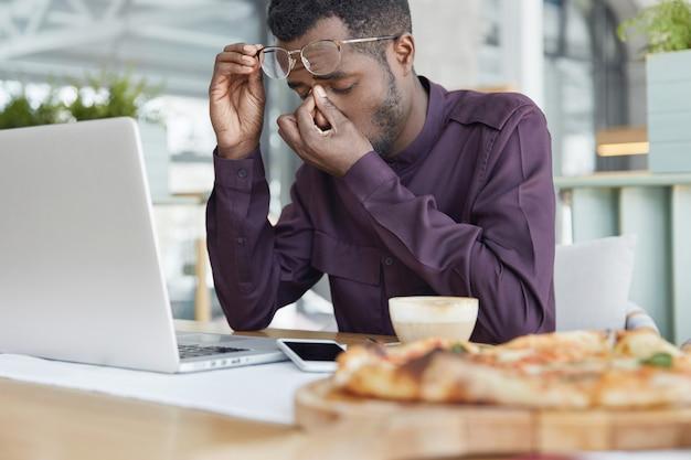 Excesso de trabalho, conceito de cansaço. empregado exausto, de pele escura, sentado em frente ao laptop, trabalhando em um novo projeto há muito tempo, tem dor nos olhos Foto gratuita