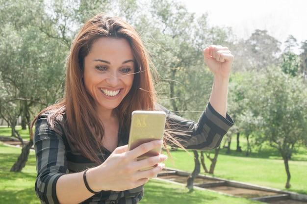 Excited eufórico senhora com smartphone comemorando grande notícia Foto gratuita