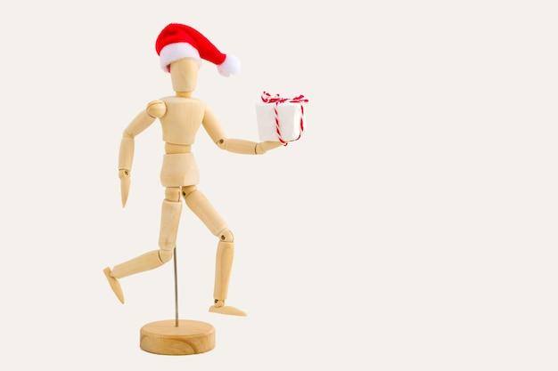 Executando a figura de madeira - manequim de arte com chapéu de papai noel vermelho com caixa de presente. negócios e conceito de design para o natal Foto Premium