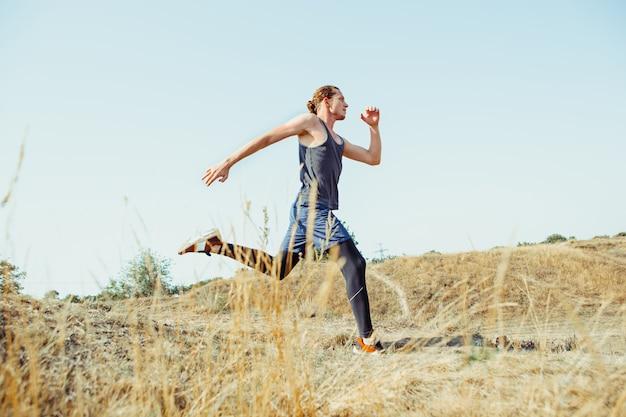 Executando o esporte. corredor de homem correndo ao ar livre na natureza cênica. ajuste a trilha de treinamento do atleta masculino musculoso correndo para a maratona. Foto gratuita