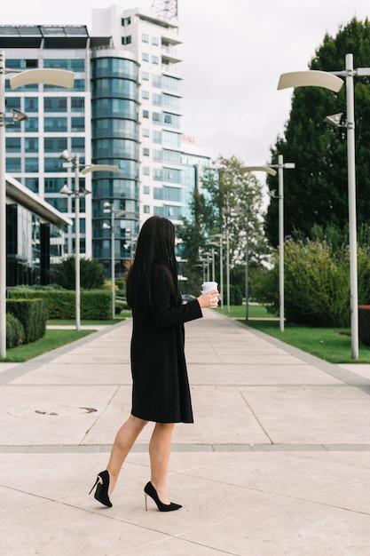 Executiva, com, eliminação, copo, andar, ligado, pavimento, frente, predios Foto gratuita
