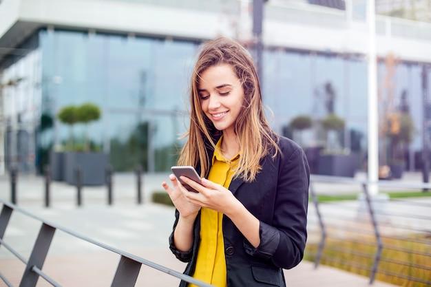 Executiva, com, um, telefone móvel, rua, com, edifícios escritório, em, a, fundo Foto Premium