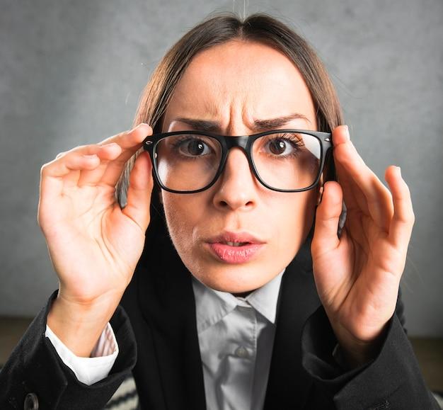 Executiva, olhar, curiosamente, através, pretas, óculos, contra, cinzento, fundo Foto gratuita