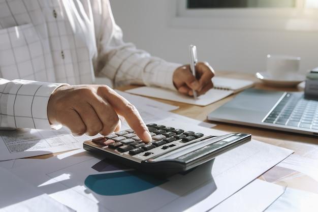 Executiva, trabalhando, escrivaninha, em, escritório, e, usando, calculadora, e, laptop, com, caneta, para, calcule Foto Premium