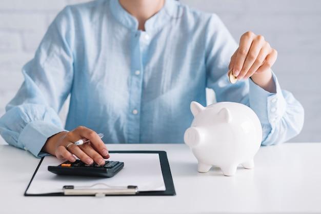 Executiva, usando, calculadora, enquanto, inserindo, moeda, em, piggybank, em, local trabalho Foto gratuita