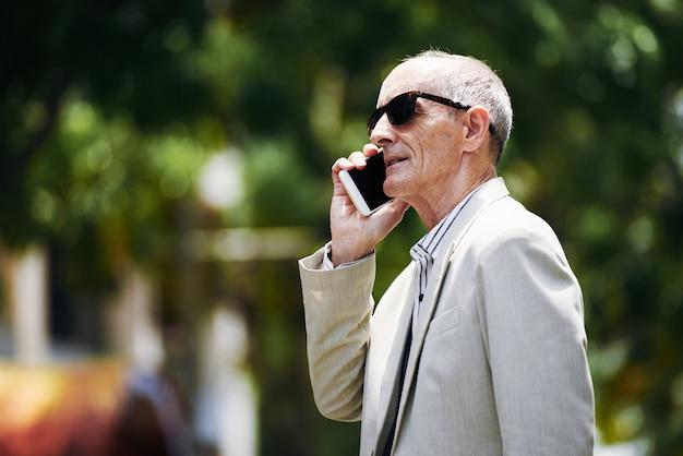 Executivo caucasiano de meia-idade em óculos de sol falando no smartphone na rua Foto gratuita