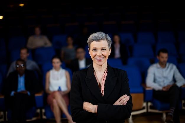 Executivo de negócios feminino com os braços cruzados no centro de  conferências | Foto Grátis
