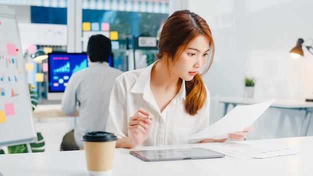 Executivo de sucesso ásia jovem empresária smart casual wear desenhando, escrevendo e usando a caneta com computador tablet digital pensando em ideias de busca de inspiração processo de trabalho em um escritório em casa moderno. Foto gratuita