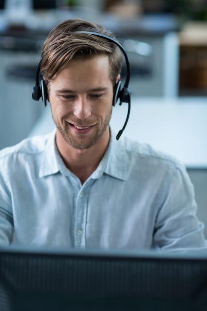 Executivo empresarial com fones de ouvido no escritório Foto Premium