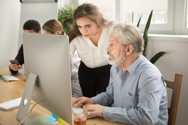 Executivo feminino, ensinando o trabalhador de escritório sênior, ajudando a explicar o trabalho do computador Foto gratuita