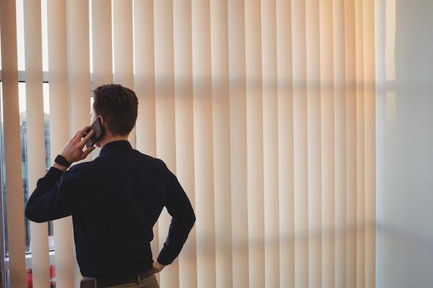 Executivo masculino falando no celular perto das cortinas Foto gratuita
