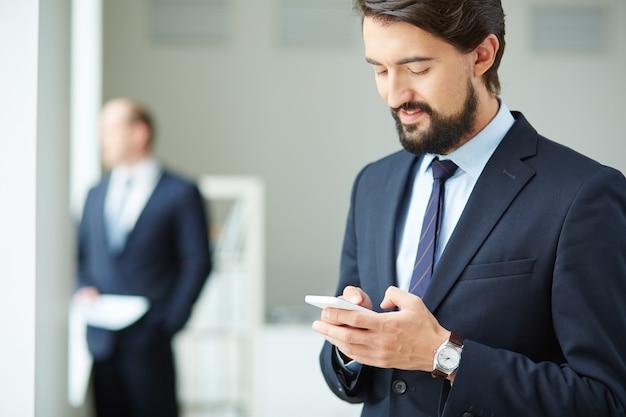 Executivo masculino usando seu telefone celular Foto gratuita