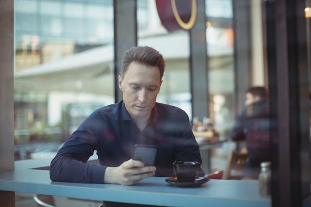 Executivo masculino usando telefone celular no balcão Foto gratuita