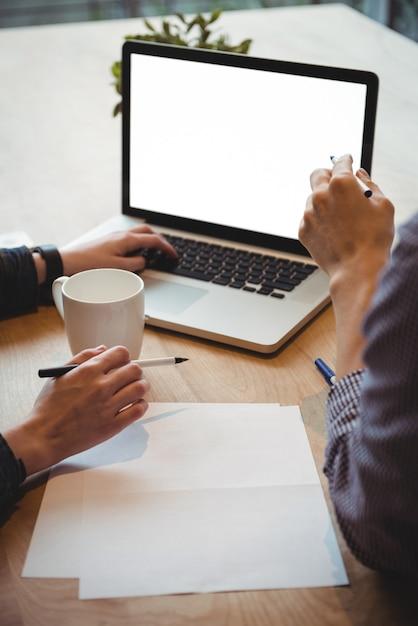 Executivos de negócios, discutindo sobre laptop Foto gratuita
