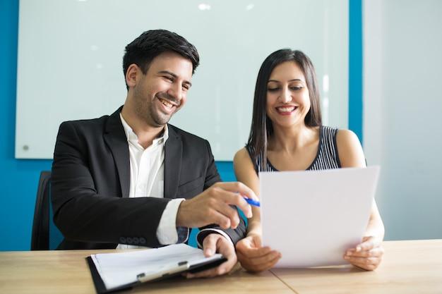Executivos de negócios positivos rindo durante a leitura de contrato Foto gratuita