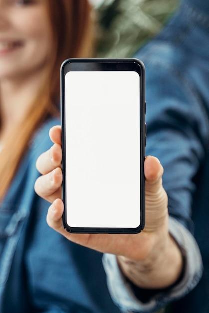 Executivos mostrando um telefone com tela vazia Foto gratuita