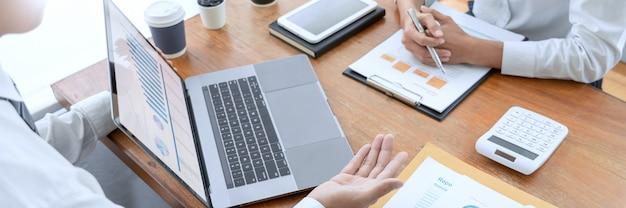 Executivos que falam discutindo com o colega de trabalho que planeja analisar tabelas e gráficos dos dados do documento financeiro na reunião e no conceito bem sucedido dos trabalhos de equipa. Foto Premium