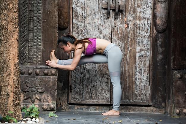 Exercício da jovem mulher do esporte com pose da ioga em casa. Foto Premium