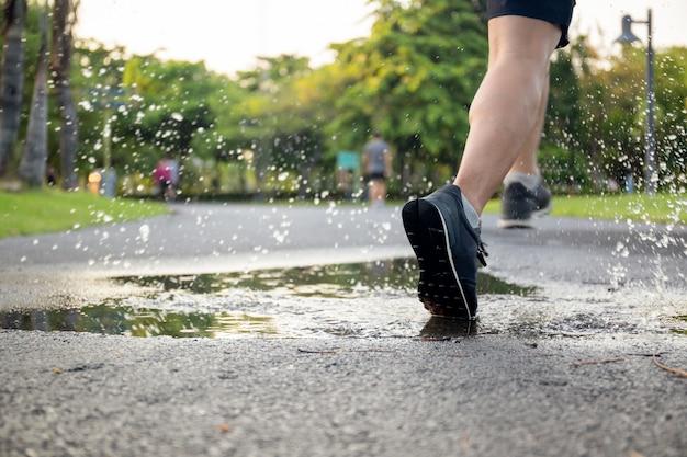 Exercício do homem que corre através da poça que espirra suas sapatas. Foto Premium