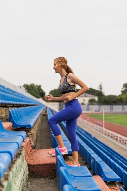 Exercício esportivo mulher nas escadas no estádio Foto gratuita