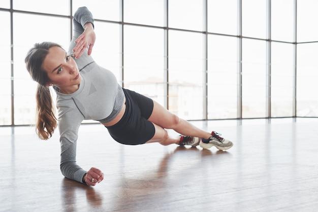 Exercícios de força e resistência. jovem esportiva fazendo exercícios na academia pela manhã Foto gratuita
