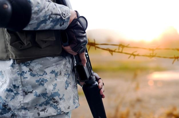 Exército de foco selecionado com arma rifle com cerca de arame de fundo desfocado Foto Premium