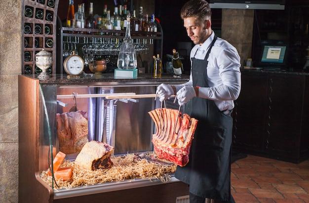 Exibição de bifes de carne seca envelhecida em açougue loja ou restaurante em um refrigerador de exibição. Foto Premium
