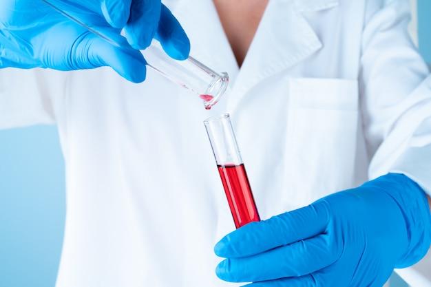 Experimentos científicos em um laboratório de química. líquidos coloridos e tubo de ensaio Foto Premium