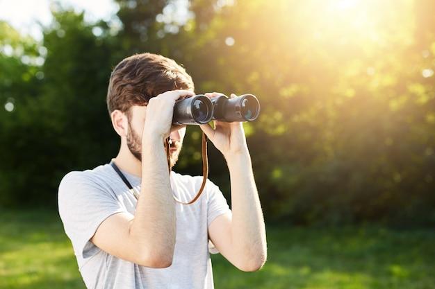 Explorador jovem turista olhando através de binóculos para distância a explorar lugares desconhecidos. viajante olhando através de binóculos Foto gratuita