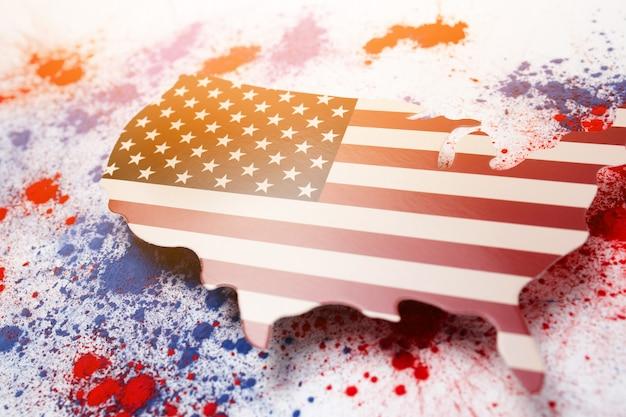 Explosão abstrata de pó colorido de holi vermelho e azul com o mapa dos eua para comemorar o dia da independência Foto gratuita