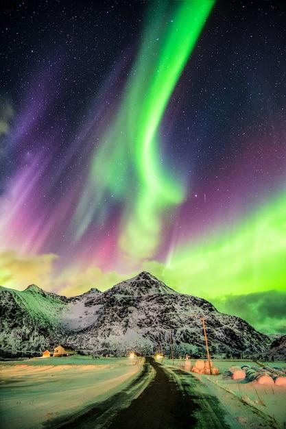 Explosão da aurora boreal (luzes do norte) sobre montanhas e estrada rural Foto Premium