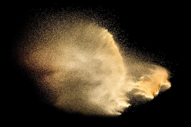 Explosão de areia isolada no preto. congele o movimento do respingo de poeira arenosa. Foto Premium