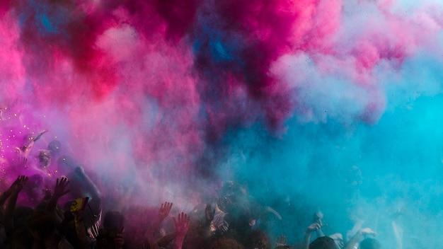 Explosão de cor holi azul e rosa sobre a multidão Foto Premium