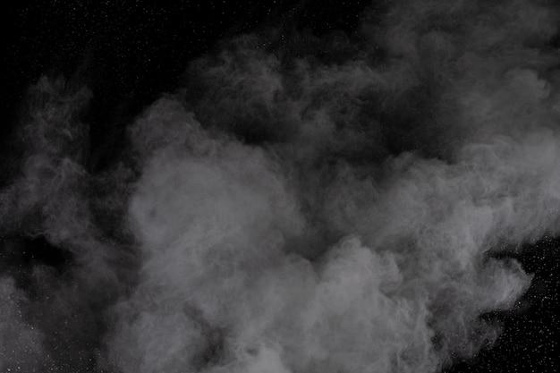 Explosão de pó branco sobre fundo preto. Foto Premium