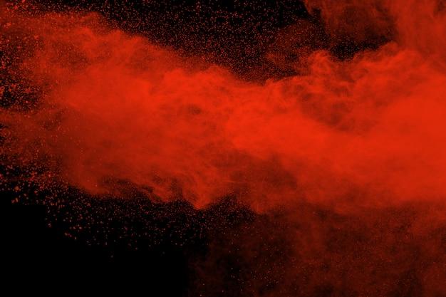 Explosão de pó de cor vermelha em fundo preto Foto Premium