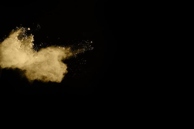Explosão de pó dourado em fundo preto. congelar movimento. Foto Premium