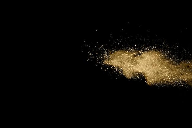 Explosão de pó dourado em fundo preto. Foto Premium
