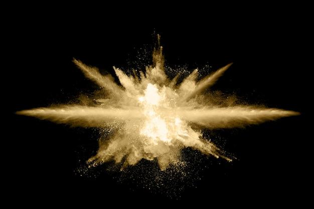 Explosão de pó dourado sobre fundo preto. Foto Premium