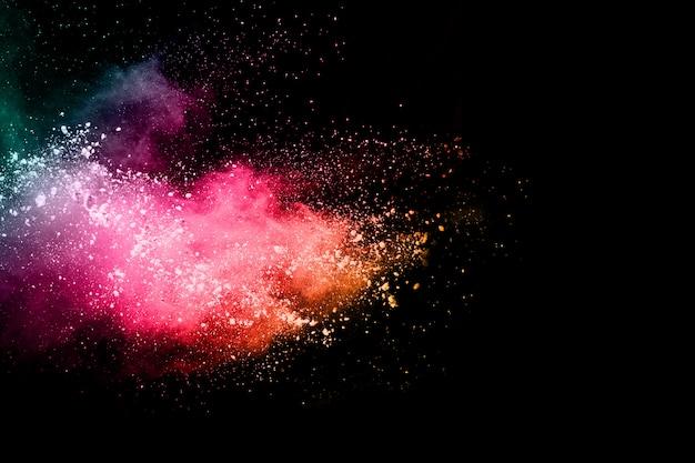 Explosão de pó multicolor em fundo preto. Foto Premium
