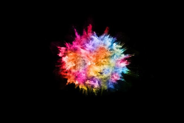 Explosão de poeira colorida abstrata em um fundo preto. Foto Premium