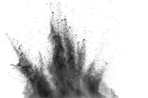 Explosão do pó preto de encontro ao fundo branco. partículas de poeira de carvão exalam no ar. Foto Premium