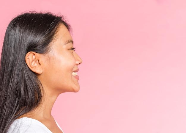 Expressão de rosto feminino mostrando felicidade lateralmente Foto gratuita